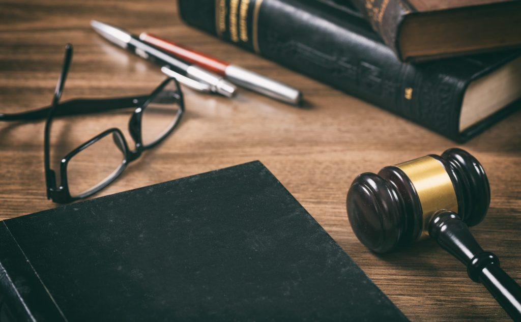 Law or auction gavel and a book, wooden office desk background. Closeup view, space for text